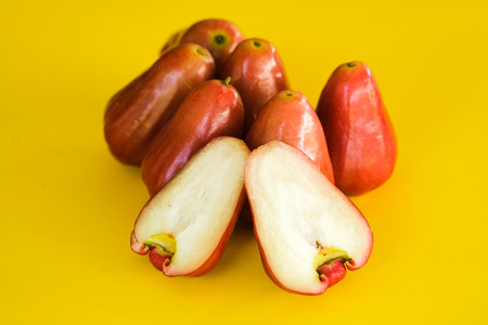 Syzygium Aqueum , Bell fruit or Jambu Air in local Malay language, is a fruit that has a shape like a bell; shot on isolated yellow background.