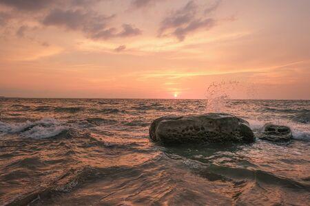 Zeegolven raken rotsen op het strand tijdens zonsondergang.