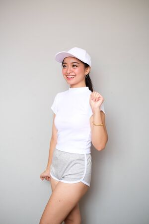 Young female Asian girl wearing a sportswear attire, shot body length, showing a happy expression Stock Photo