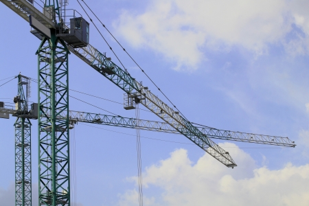 Two construction cranes is working on the construction site