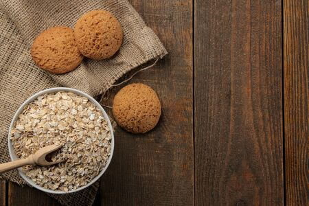 Dry oatmeal and oatmeal cookies in a white bowl and a wooden spoon. food. healthy food. on a brown wooden table. top view with space for inscription Stock fotó