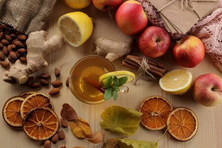 Autumn composition with hot tea, fruits and yellow leaves on a natural wooden table. view from above Foto de archivo