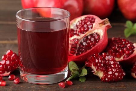 Pomegranate juice in a glass with fresh pomegranates around on a brown wooden table Stockfoto