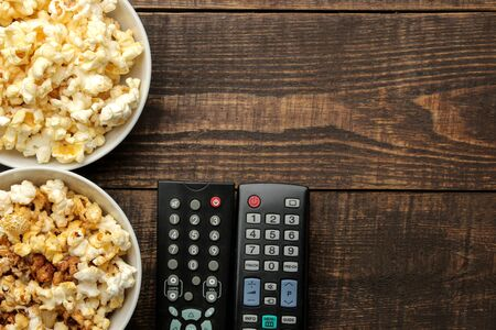 Popcorn and TV remote on a brown wooden background. concept of watching movies at home. top view with space for text
