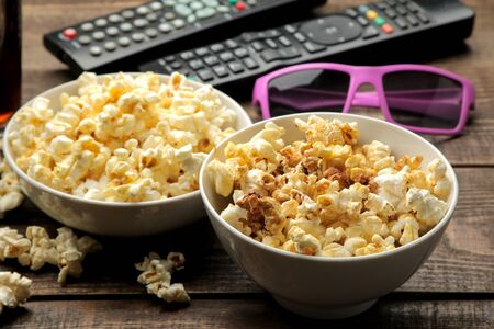 Popcorn, 3D glasses and TV remote on a brown wooden background. concept of watching movies at home.
