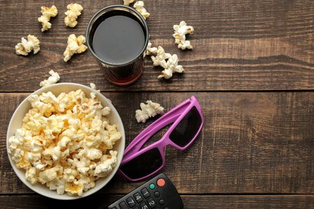 Popcorn, 3D glasses and TV remote on a brown wooden background. concept of watching movies at home. view from above