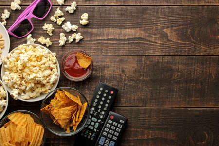 Popcorn and various snacks, 3D glasses, TV remote on a brown wooden background. concept of watching movies at home. top view with space for text