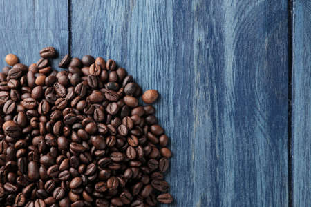 Frame of roasted coffee beans on a blue wooden table. view from above. space for text