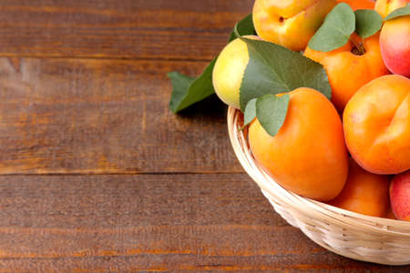 A lot of fresh, ripe apricot in a wicker basket on a brown wooden background
