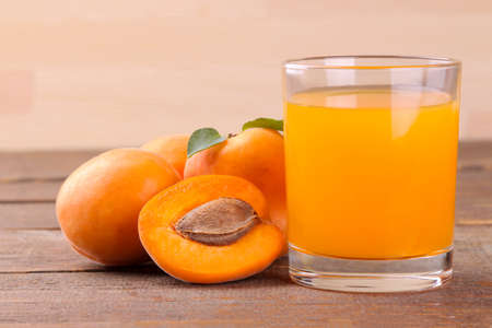 Apricot juice in a glass cup next to fresh apricots on a brown wooden background