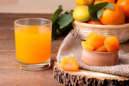 Dried apricots, apricot juice and fresh apricots on a brown wooden background