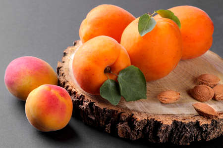 Fresh, ripe apricots on a wooden stand on a black background