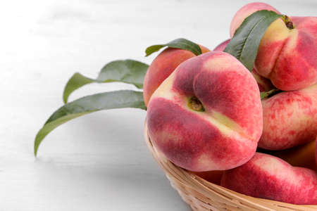 Ripe large figs peach in a basket on a white wooden background close-up