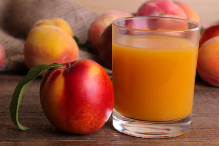 Peach juice in a glass next to a fresh peach closeup on a brown wooden background