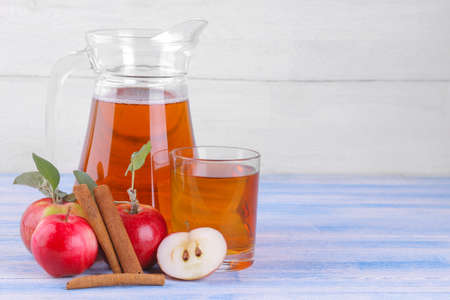Apple juice in a jug and a glass next to fresh apples and cinnamon sticks on a blue wooden table and on a white wooden background Banque d'images