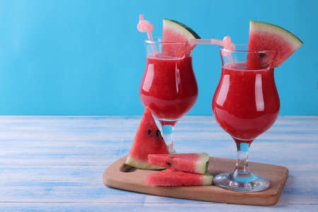Watermelon smoothies with a slice of watermelon and a straw on a blue wooden table with a place for writing