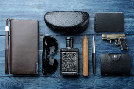 Men's Accessories.men's style. Glasses, perfume, wallet, notebook, cigar and business card holder on a blue wooden background.lat lay