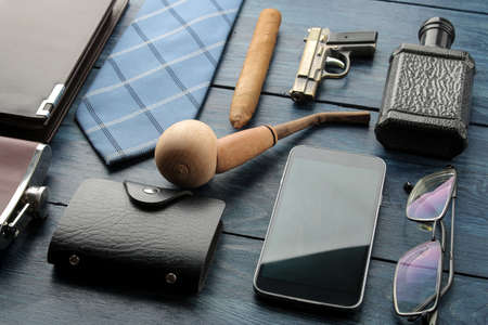 Men's Accessories. men's style. smartphone, business card holder, perfume, smoking pipe, purse on a blue wooden background.