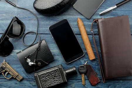 Men's Accessories.men's style. Glasses, business card holder, cigar, smartphone, notebook, headphones, and a pistol-lighter on a blue wooden background. Lay lay. 스톡 콘텐츠
