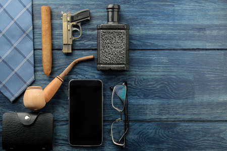 Men's Accessories.men's style. Smartphone, perfume, smoking pipe glasses, cigar and business card holder. on blue wooden background. lay. with space for text