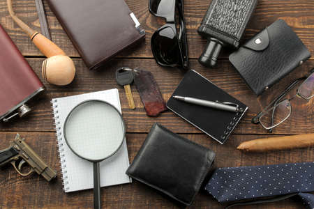Men's Accessories. men's style. purse, flask, smoking pipe, perfume, business card holder, notebook, keys, glasses, cigar, on a brown wooden background. flat lay. 스톡 콘텐츠