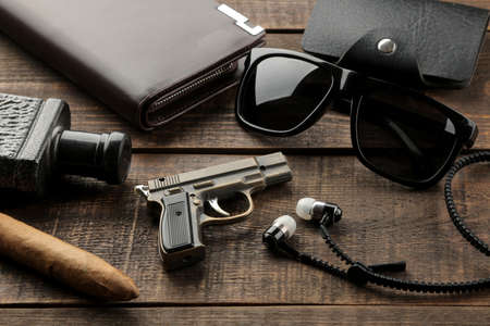 Men's Accessories. men's style. Cigar, perfume, wallet, glasses, business card holder, headphones on a brown wooden background.