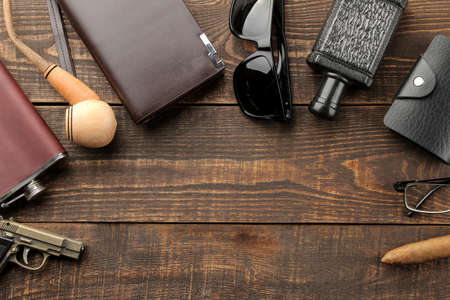 Men's Accessories. men's style. purse, flask, smoking pipe, perfume, business card holder, glasses, cigar, on a brown wooden background. flat lay. with space for text. frame