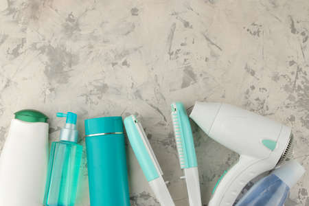 Various hair care products and various accessories, hair dryer, curling iron. on a light background. hair cosmetics. top view with space for text