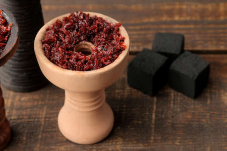 Clay bowls for hookah with tobacco on a brown wooden table. accessories for hookah. close-up