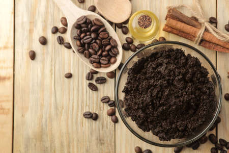 homemade coffee scrub in the face and body bowl and various ingredients for making scrub on a wooden table. spa. cosmetics. care cosmetics. top view with space for text