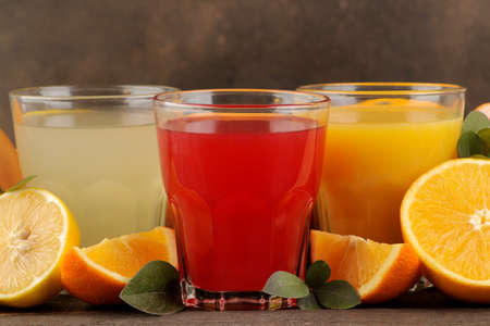 Citrus juices. Lemon, grapefruit and orange juice with fresh fruits on a brown wooden table