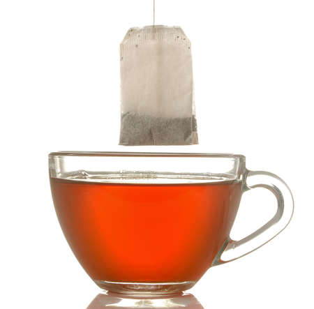 glass cup with tea and tea bag close up on white isolated background