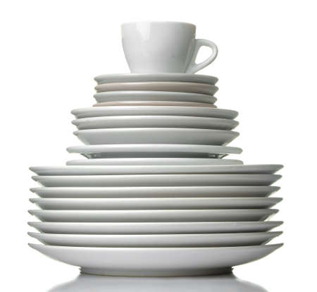 A stack of dishes. Dinnerware plates and cup on a white isolated background. close-up.