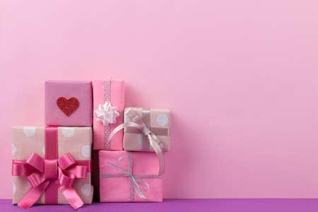 礼品盒。在一个柔和的桃红色和淡紫色背景的礼物。假期。情人节。妇女节。母亲节。文本的空间