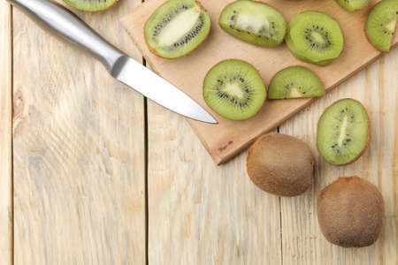 Delicious ripe lots of kiwi fruit and kiwi cutaway cut on a natural wooden table. top view. space for text