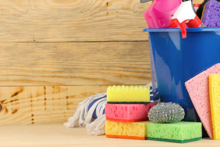 Bottles with detergent and cleaning tools in a bucket on a natural wooden background. cleaning. cleaning products. place for text. free place