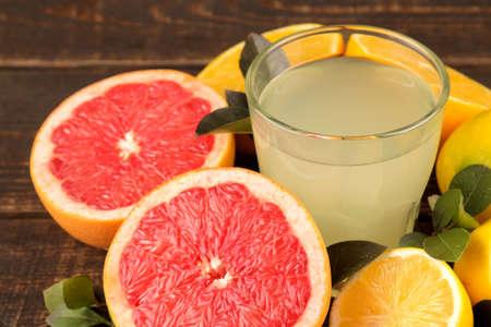 Citrus fruit. Various citrus fruits with leaves of lemon, orange, grapefruit and lemon juice on a brown wooden table.