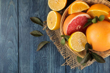 Citrus fruit. various citrus fruits with leaves of lemon, orange, grapefruit in a basket and orange juice on a blue wooden table. top view