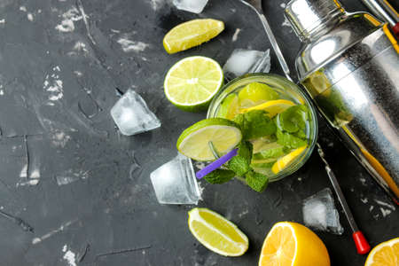 Mojito cocktail in a glass glass with lime, mint and lemon and bar accessories on a dark concrete background. cooking mojito. top view. free place