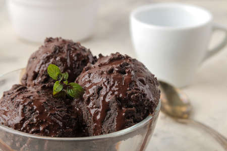 Chocolate ice cream with liquid chocolate on a light concrete background.