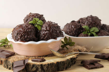 Chocolate ice cream with liquid chocolate and a mint leaf on a natural wooden background.