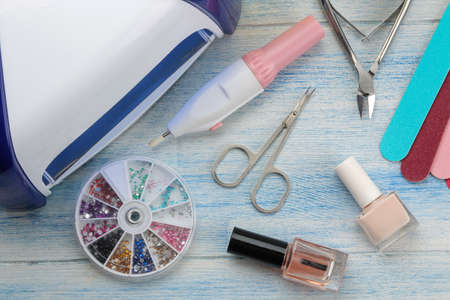 Manicure. nail polishes, UV lamp and various accessories and tools for manicure on a blue wooden table. top view