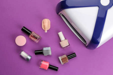 Manicure. UV lamp and nail polish on a trendy purple background. Manicure accessories and tools for nails. top view