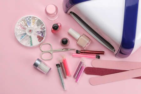 Manicure. nail polishes, UV lamp and various accessories and tools for manicure on a trendy pink background. top view Imagens