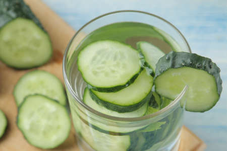 water with cucumber. Refreshing diet water with cucumber and mint in a glass beaker against a blue background. detox drink concept. summer refreshing drink.