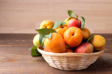 A lot of fresh, ripe apricot in a bag on a brown wooden background