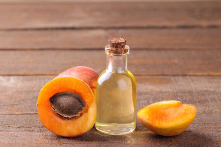 Apricot seed oil next to fresh apricots on a brown wooden background.