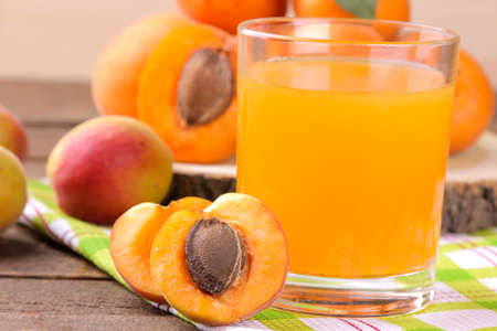 Apricot juice in a glass cup next to fresh apricots on a brown wooden background Reklamní fotografie - 151111442