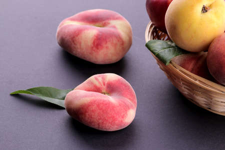 Many different varieties of peaches in a wicker basket on a black background.