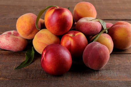 composition of many varieties of peach on a brown wooden background. fruits.